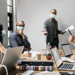Business people wearing masks in coronavirus meeting, the new no